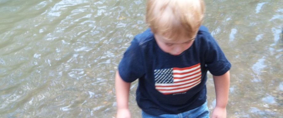 boy wades in river